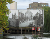 A billboard on the canal publicizes Amsterdam's renovation plans.