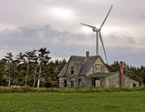 An old abandoned  house in Prince Edward Island contrasts with the modern wind turbine.