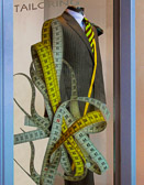 A tailor shop display made interesting with  the use of a tape measure.