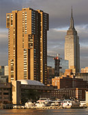The Empire State Building and an East River marina glow in the early morning sun.