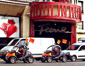 High gas prices inspire the design of cars like these driving past the Moulin Rouge.