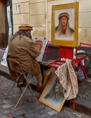 A self portrait artist hopes to sell his work at Place Tertre in Montmartre.