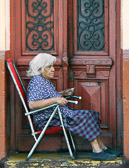 This old woman  spends the day by her door watching the passing parade.
