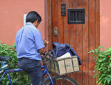 The mailman delivers the mail by bicycle in the city of Lima.
