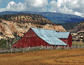 An old barn set among  older rocks, golden fields and a big western sky.